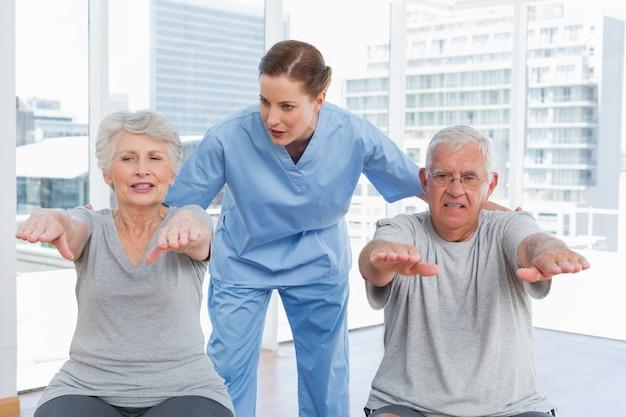 Terapeuta feminina, auxiliando o casal sênior com exercícios