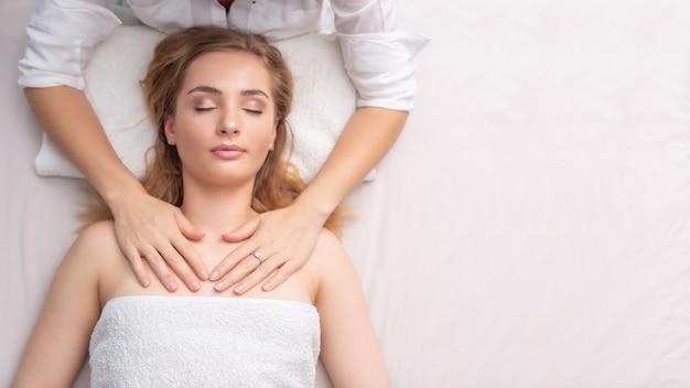Terapeuta feminina, curando uma jovem mentirosa pelo toque das mãos em um fundo branco.