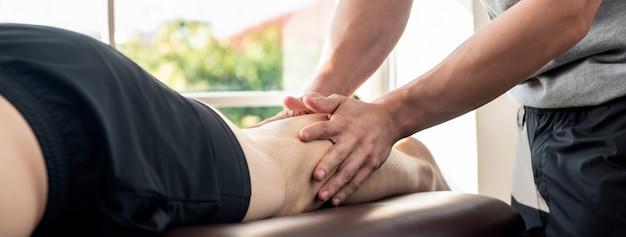 Terapeuta masculina, dar, perna, massagem, para, atleta, paciente, cama, em, clínica