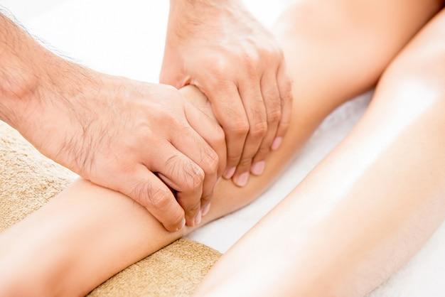 Terapeuta masculina que dá tratamento tailandês da massagem da perna a uma mulher no spa