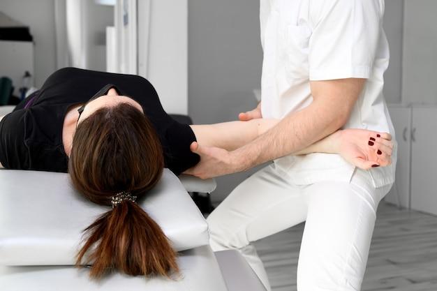 Terapeuta masculino fazendo massagem para alívio da dor no ombro de uma paciente do sexo feminino na clínica de fisioterapia.