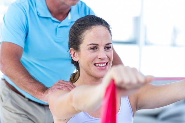 Terapeuta massageando mulher grávida alegre