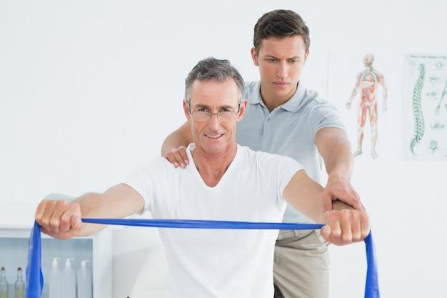 Terapeuta massageando o ombro do homem no hospital