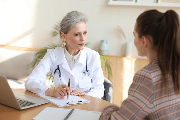Terapeuta médica feminina de meia idade em consulta com o paciente no consultório.