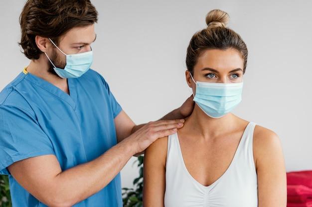 Terapeuta osteopata masculino com máscara médica verificando o pescoço de uma paciente