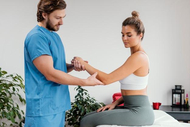 Terapeuta osteopata masculino verificando o movimento do cotovelo de uma paciente