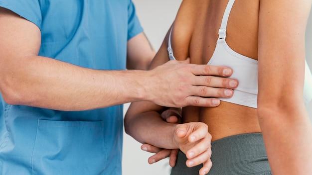 Terapeuta osteopata masculino verificando osso da escápula de paciente do sexo feminino