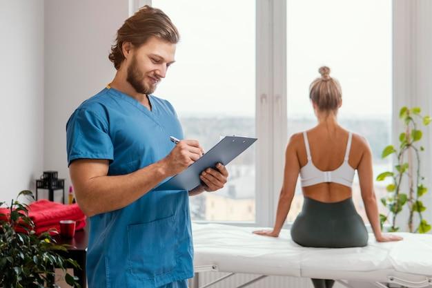 Terapeuta osteopático masculino com prancheta e paciente do sexo feminino no consultório