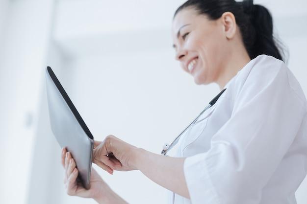 Terapeuta positivo, animado e habilidoso, apreciando o horário de trabalho na clínica, sorrindo e usando o tablet