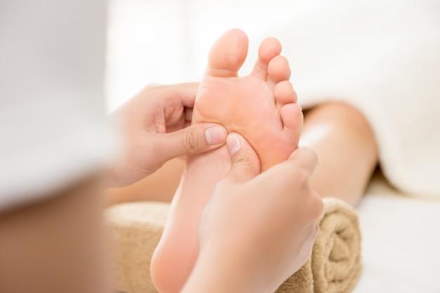 Terapeuta profissional dando massagem tailandesa tradicional nos pés para uma mulher