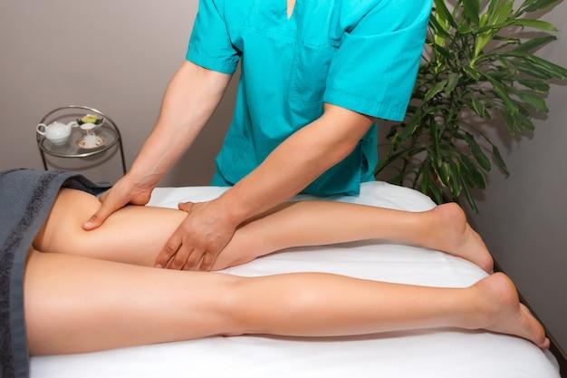 Terapeuta profissional dando tratamento de massagem relaxante para uma mulher no spa.