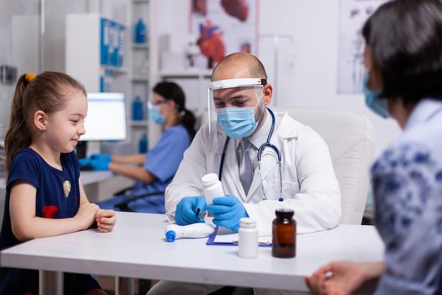 Terapeuta profissional escolhendo medicamentos para doenças médicas. especialista em tratamento de doenças usando máscara de proteção e viseira contra coronavírus, prestando serviços de saúde durante a pandemia global