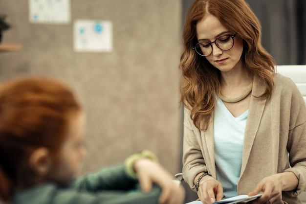 Terapeuta profissional. mulher séria e inteligente olhando para suas anotações enquanto pensa em seu paciente