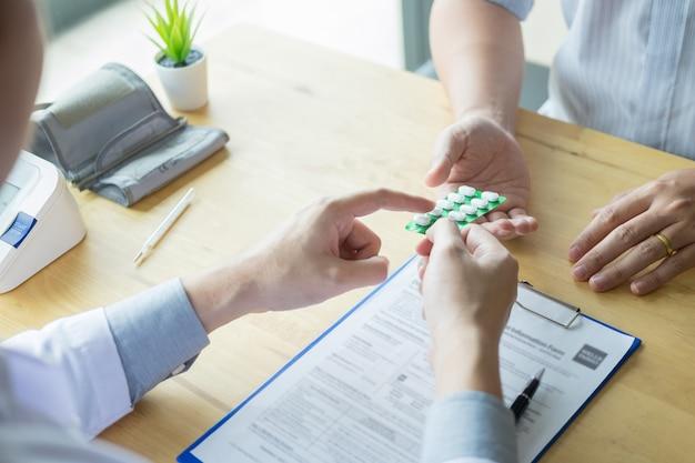 Terapeuta que consulta ao paciente masculino paciente sobre os comprimidos que escrevem sua droga de prescrição médica no escritório.