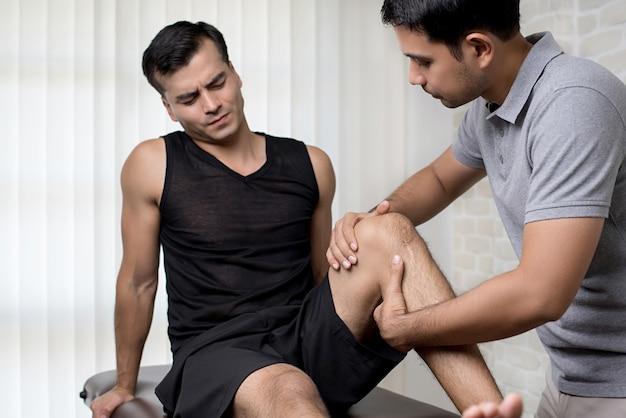 Terapeuta que trata o joelho ferido do paciente do sexo masculino atleta na clínica