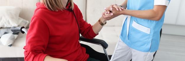 Terapeuta segurando a mão de uma mulher com deficiência em close-up de máscara protetora médica