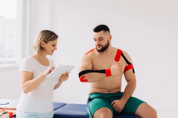 Terapeuta usando tablet digital, explicando informações médicas e dando alguns conselhos para um paciente.