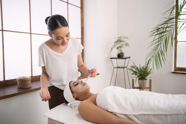 Terapia anti-idade. cosmetologista habilidosa e alegre olhando para seu cliente enquanto aplica uma máscara anti-idade em seu rosto
