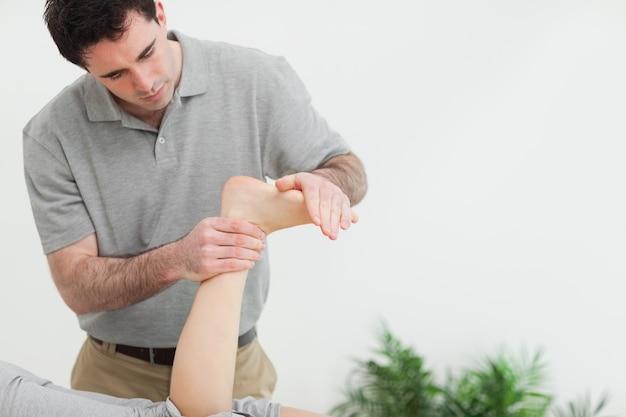 Terapia de cabelo castanho esticando o pé de um paciente