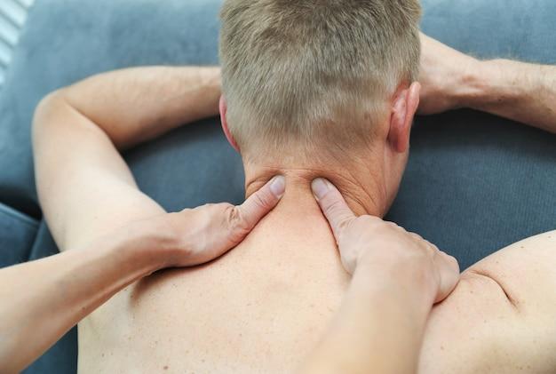 Terapia de massagem de saúde nos ombros de um homem
