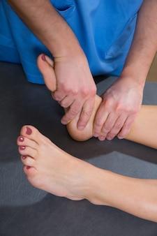 Terapia de mobilização articular do tornozelo de médico homem para mulher