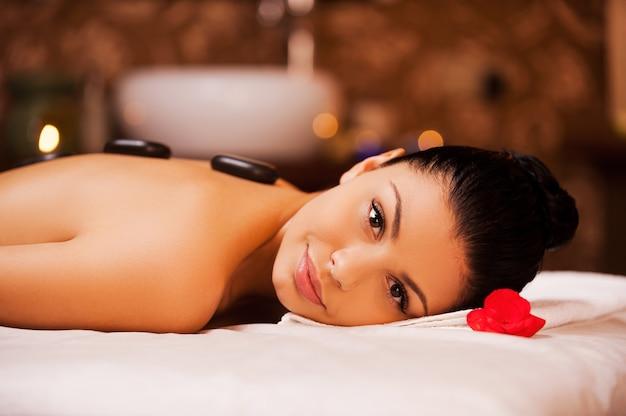 Terapia de pedras. vista lateral de uma bela jovem sem camisa deitada na mesa de massagem e olhando para a câmera com pedras de spa nas costas
