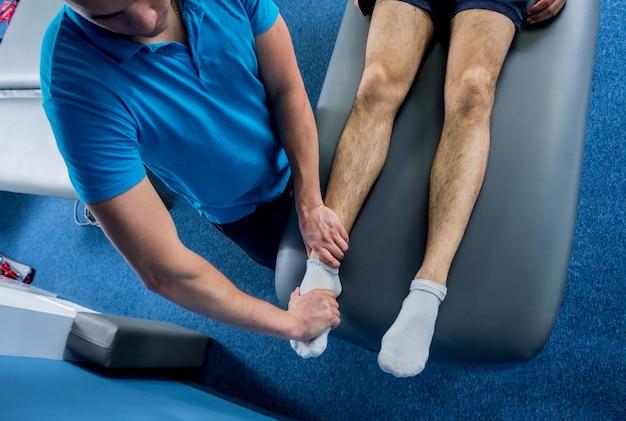 Terapia de reabilitação. fisioterapeuta trabalhando com jovem paciente do sexo masculino