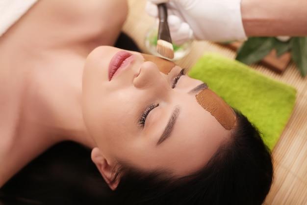 Terapia de spa para jovem com máscara cosmética no salão de beleza