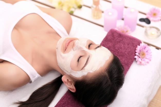Terapia de spa para jovem com máscara facial no salão de beleza