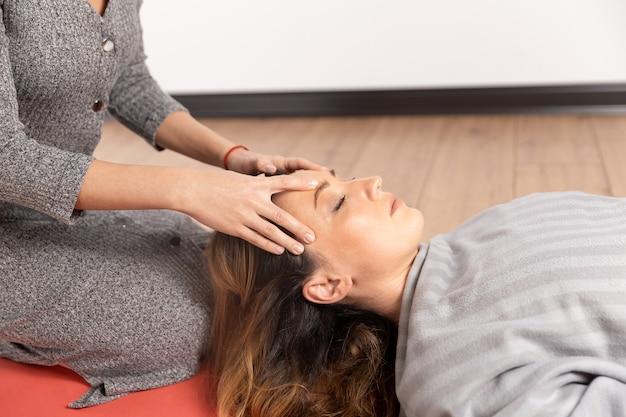 Terapia especial. processo de massagem de relaxamento da cabeça. mulher fazendo massagem com as mãos.