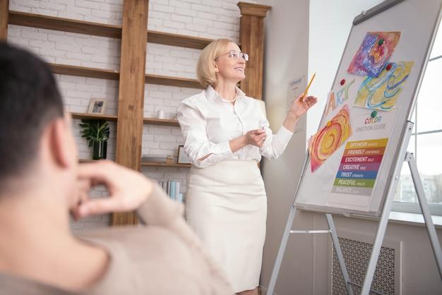 Terapia expressiva. psicólogo sênior entusiasmado em pé enquanto fala com um colega Foto Premium