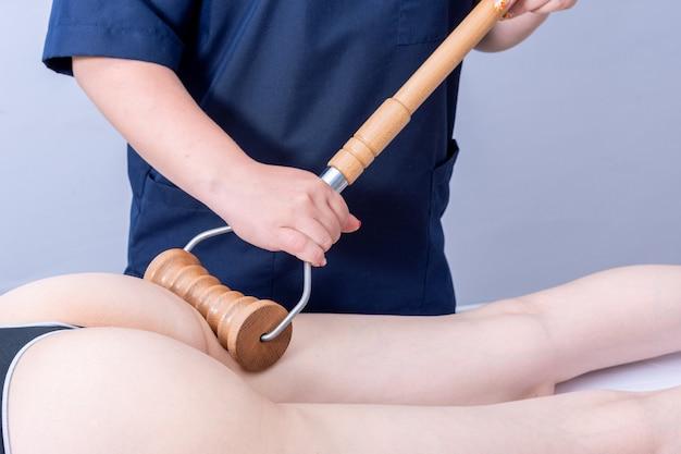 Terapia madero, massagem anticelulite, massagem de drenagem linfática - mulher recebendo massagem spa da parte de trás da coxa em um salão de beleza usando um massageador de rolo de madeira. conceito de cuidados com o corpo