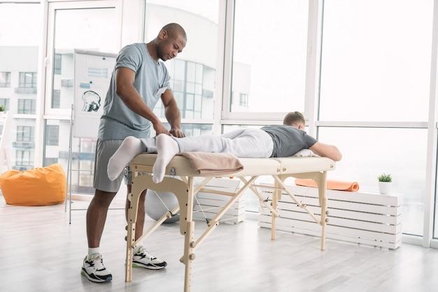 Terapia moderna. jovem sério e agradável fazendo uma massagem enquanto trabalhava no centro de reabilitação