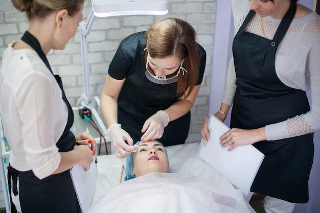 Terapia profissional de cuidados da pele. esteticistas femininas trabalhando com cliente em clínica moderna.