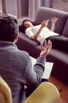 Terapia psicológica. homem inteligente e simpático fazendo perguntas ao paciente durante uma sessão de terapia psicológica