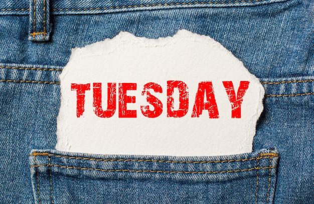 Terça-feira em papel branco no bolso da calça jeans azul