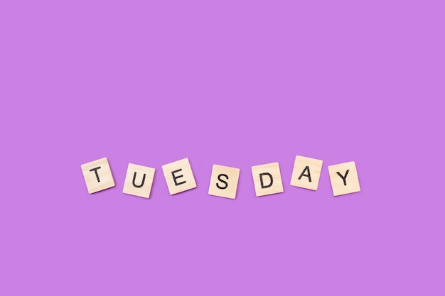 Terça-feira, escreva com cubos de letras de madeira em um fundo roxo
