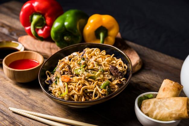 Teriyaki de carne delicioso com macarrão udon e sementes de gergelim enfeite na mesa de madeira