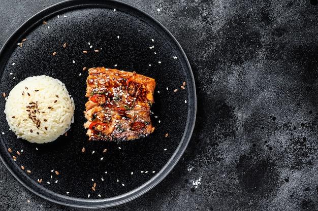 Teriyaki japonês grelhado filé de truta de vidro envidraçado em molho delicioso com um prato de arroz. superfície preta. vista do topo. copie o espaço