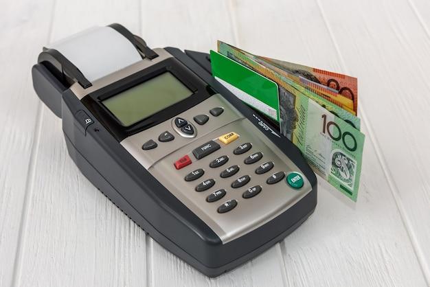 Terminal bancário com cartão de crédito e dólares australianos