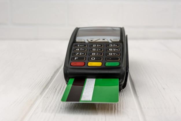 Terminal bancário com cartão de crédito na mesa de madeira