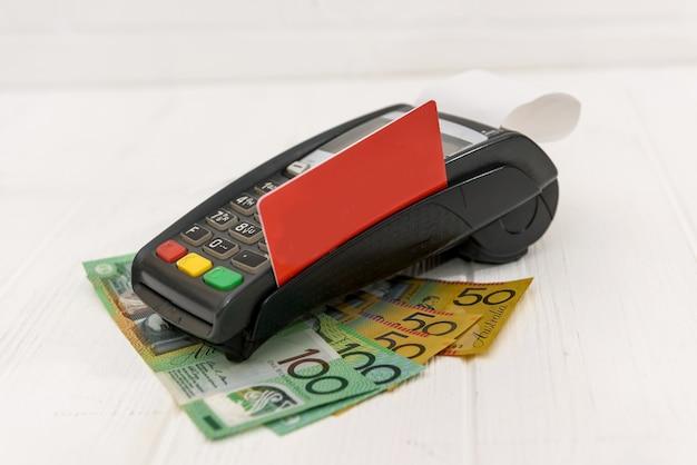 Terminal bancário com cartão e dólares australianos no carrinho