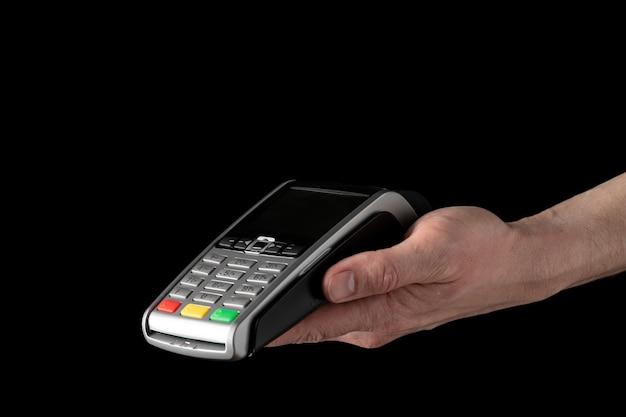 Terminal bancário para pagamento com cartões de crédito em mãos sobre fundo preto