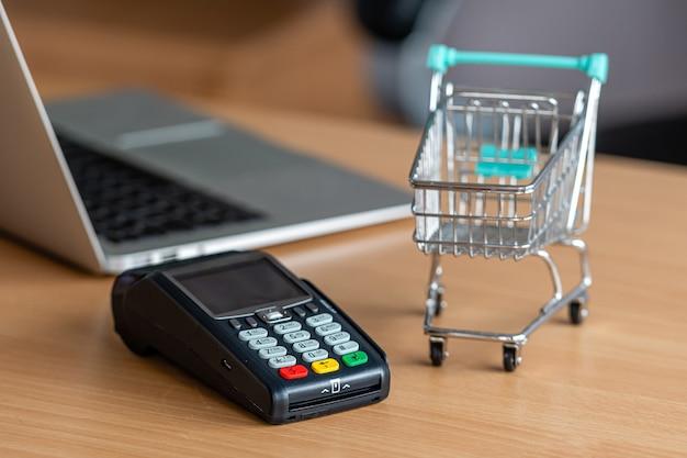 Terminal de cartão de crédito na mesa da loja com cartão de crédito, laptop e mini carrinho de compras