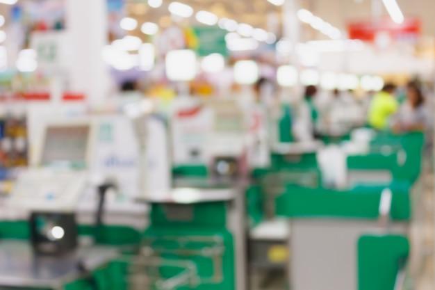 Terminal de pagamento de checkout de supermercado com fundo desfocado de clientes