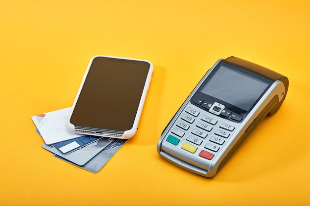 Terminal de pagamento sem fio para pagamentos com cartão de crédito ou nfc, telefone celular e cartão de crédito em fundo amarelo