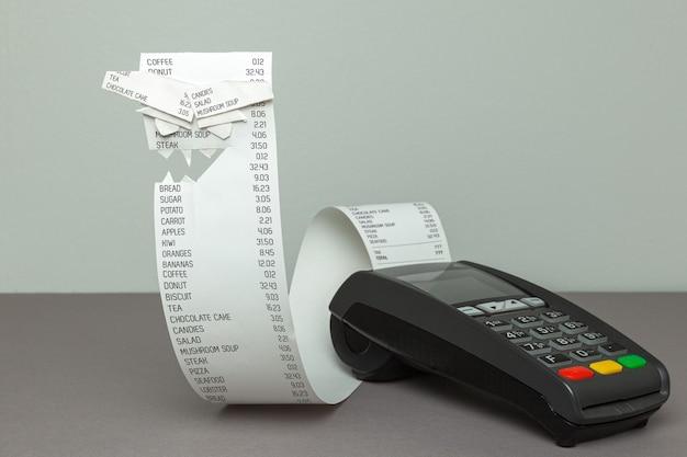 Terminal de pontos de fatura de papel zangado com fita de papel em um fundo cinza rosto assustador feito de papel