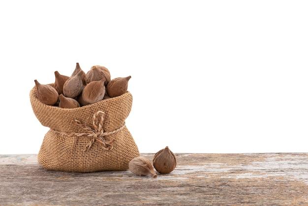 Terminalia bellirica ou frutas beleric myrobalan em saco na mesa de madeira com traçado de recorte.
