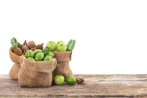 Terminalia bellirica, terminalia chebula e phyllanthus emblica frutos em saco sobre a mesa de madeira com traçado de recorte.