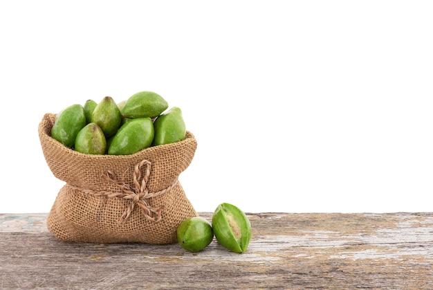 Terminalia chebula ou frutas chebulic myrobalans em saco na mesa de madeira com traçado de recorte.